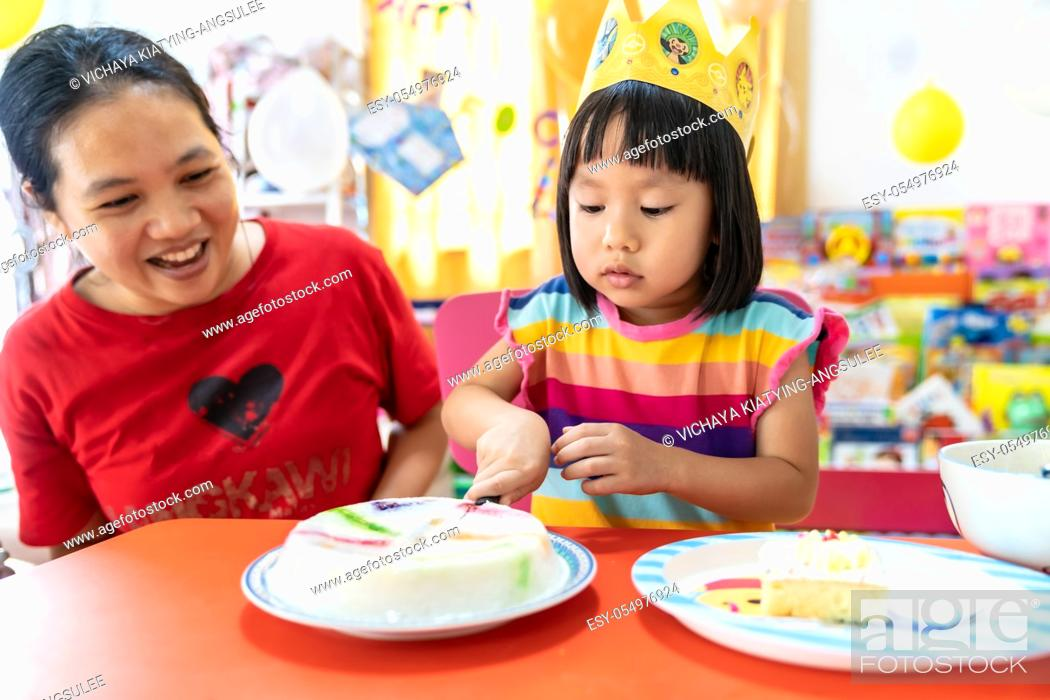 Stock Photo: Asian girl kid cutting her birthday cake celebrate with mom alone because city lockdown while COVID-19 Pandemic. Celbration and quarantine concept.