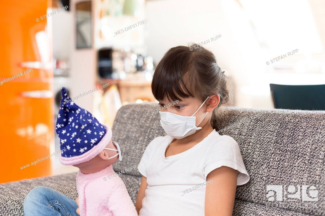 Stock Photo: Little girl with protective mask sitting on couch at home playing with doll.