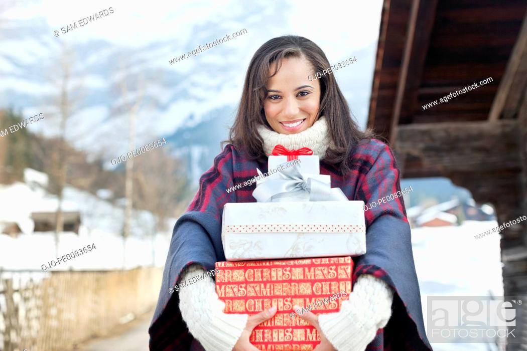 Stock Photo: Portrait of smiling woman holding Christmas gifts.