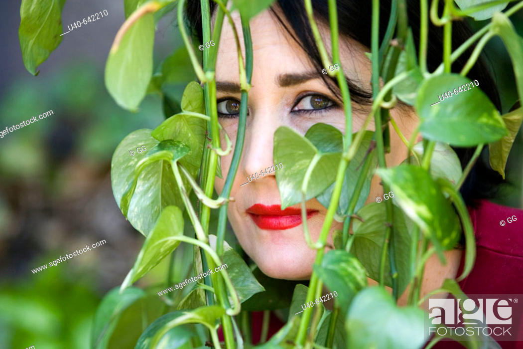 Stock Photo: Woman looking through ivy.