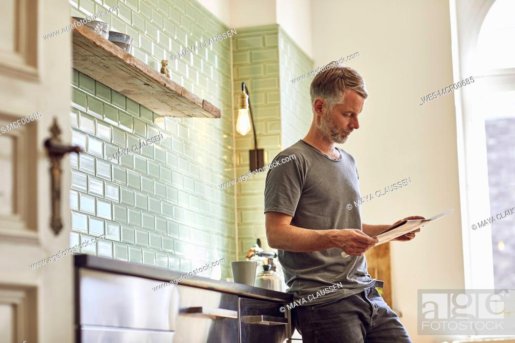 Stock Photo: Mature man reading newspaper in kitchen at home.