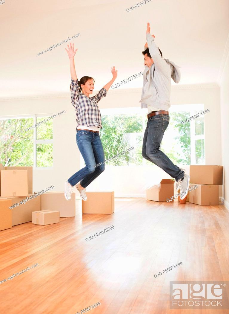 Stock Photo: Excited couple jumping in new house.