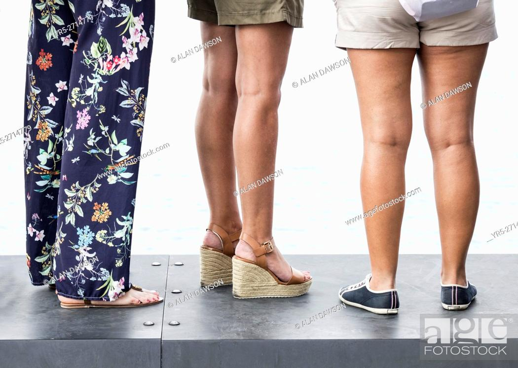 Stock Photo: Three woman wearing different kinds of footwear: heels and flat.