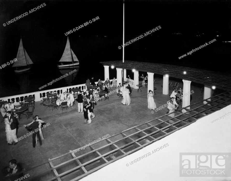 Stock Photo: Bermuda: c. 1927. Couples dancing on the Marine Pavillion of the Inverurie Hotel at night. The lights of Hamilton are seen in the background.