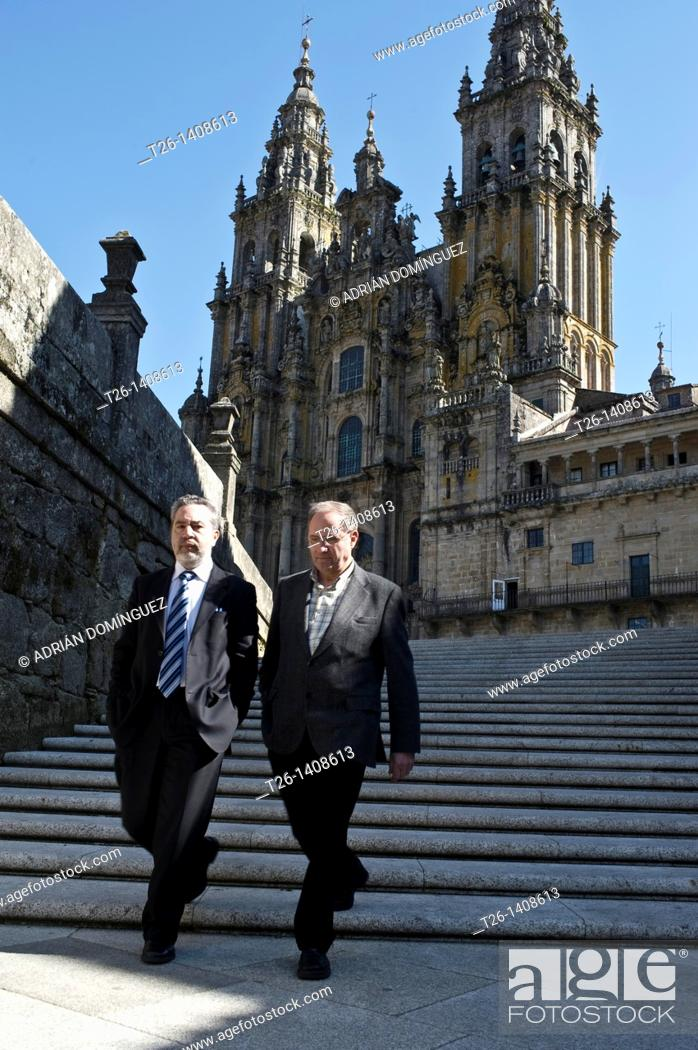 Stock Photo: Two men walk with the Cathedral behind in Santiago de Compostela. Galicia, Spain.
