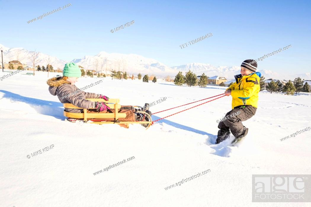 Stock Photo: Children (8-9) playing with sled in snow.