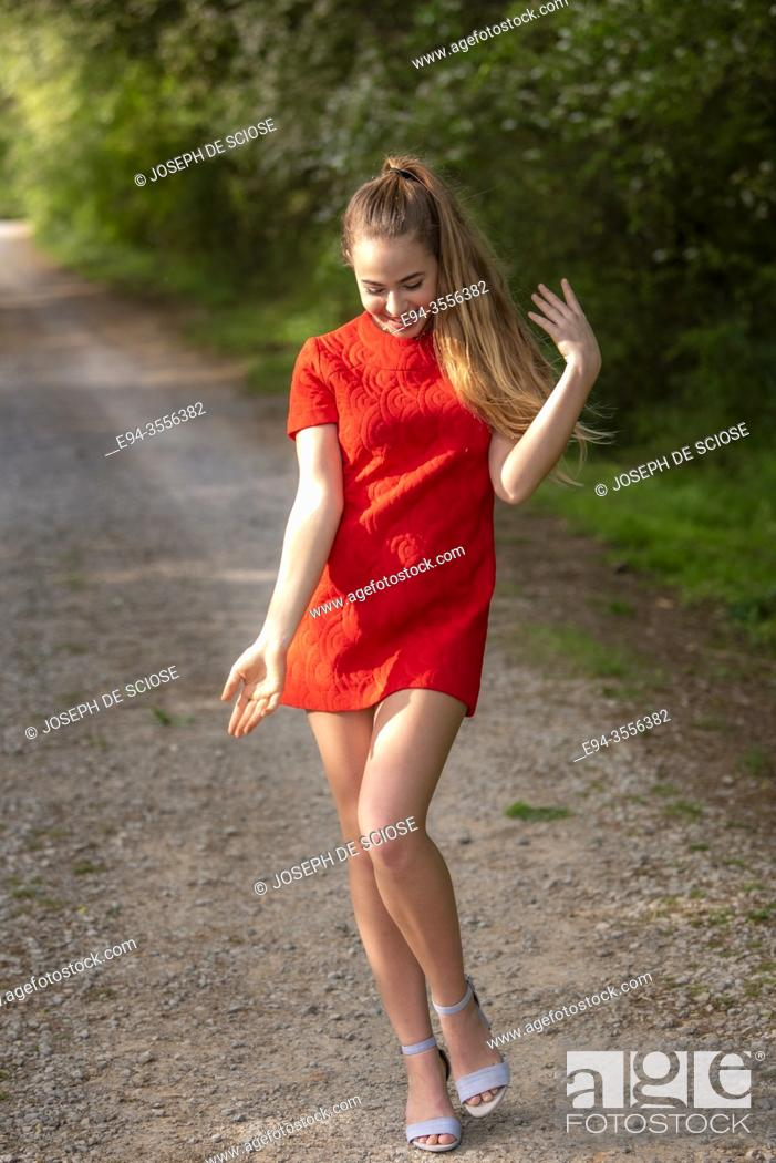 Photo de stock: A 14 year old brunette girl wearing a short red dress on a dirt country road making a silly gesture.