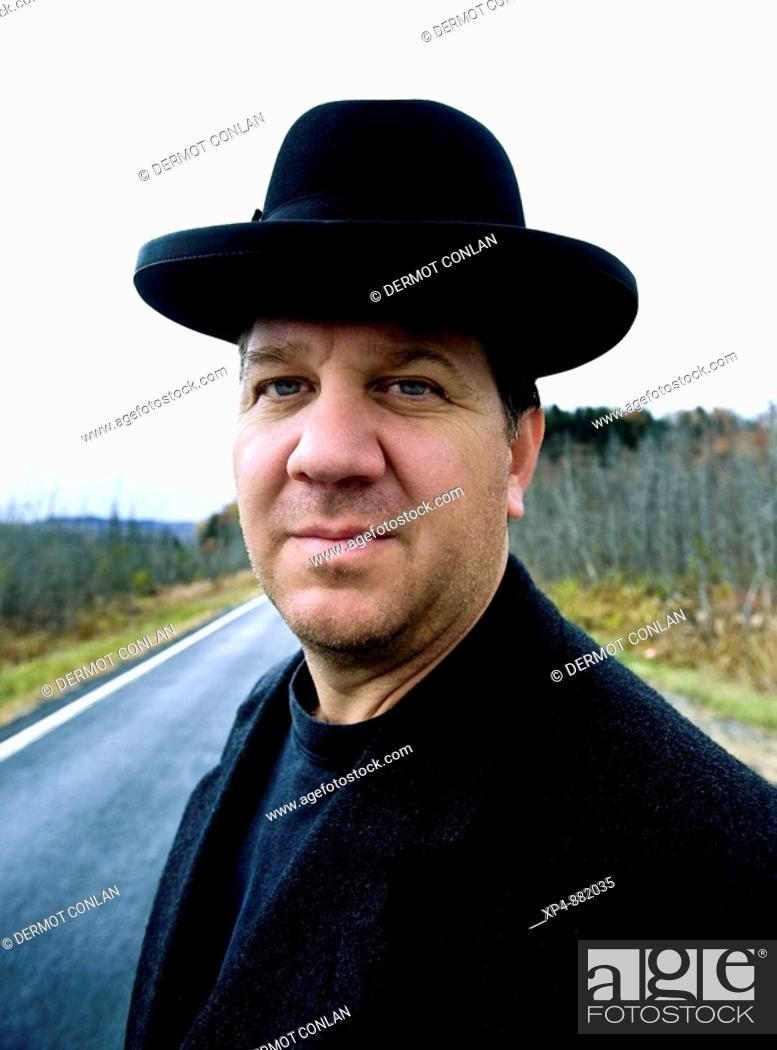 f09493100d4 Stock Photo - Portrait of a man in a black hat and overcoat standing on a country  road.