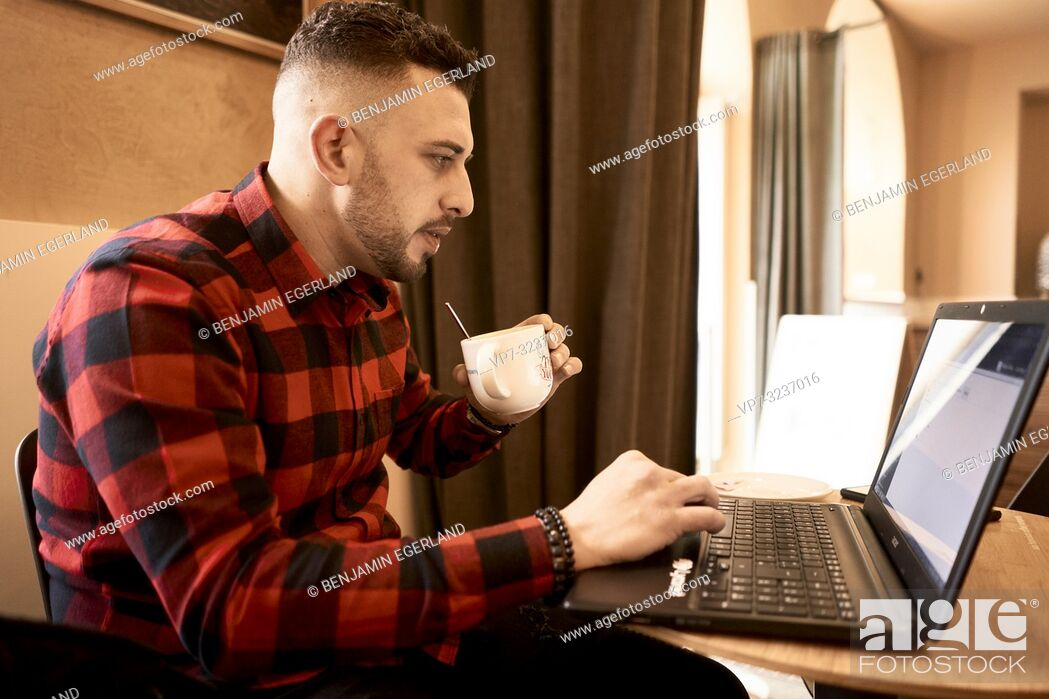 Stock Photo: man working with laptop indoors in café, drinking coffee, casual shirt, freelancer, self employee, Greek ethnicity, in Munich, Germany.