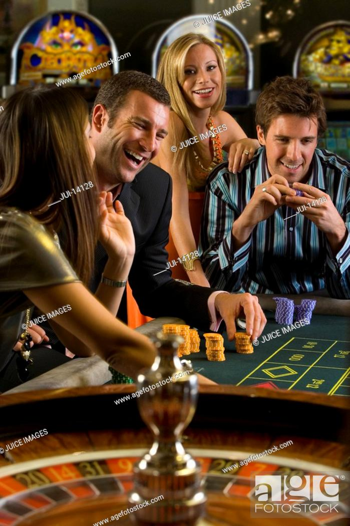 Stock Photo: Men and women gambling at roulette table, smiling.