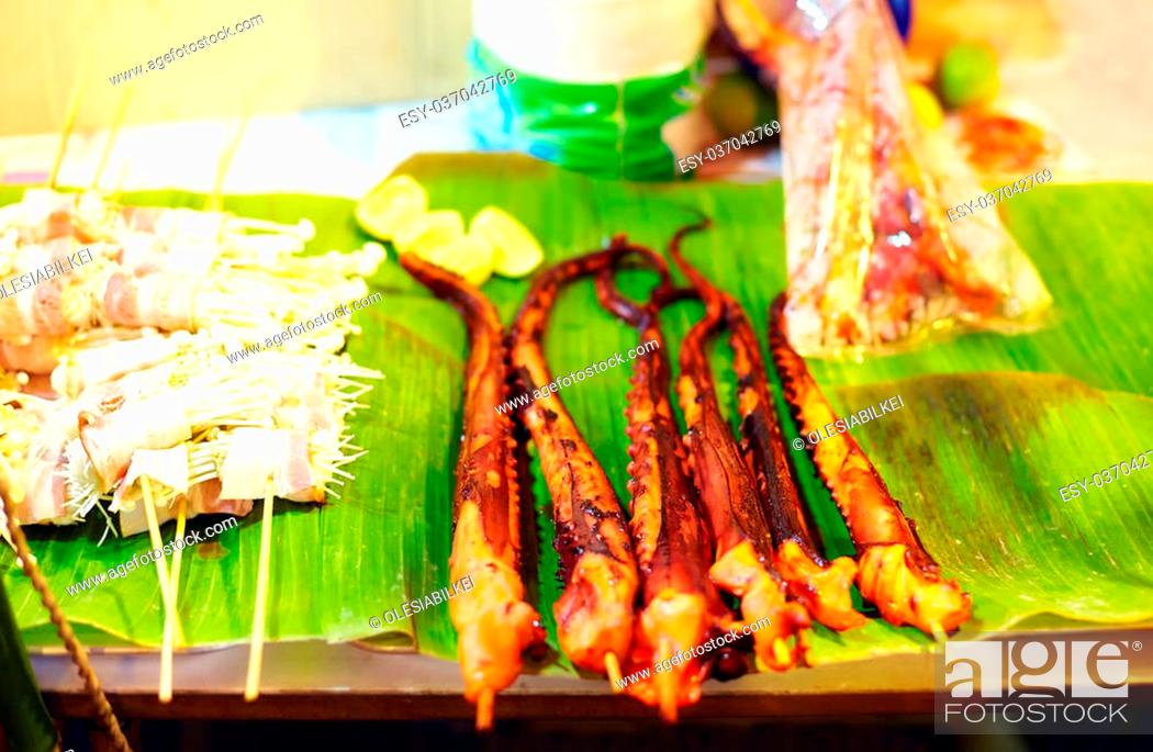 Stock Photo: fried tentacles of octopus at street market in Asia.