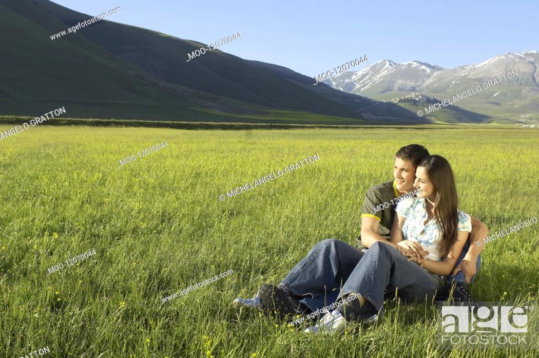 Stock Photo: Young couple sitting in mountain field looking at view full length.
