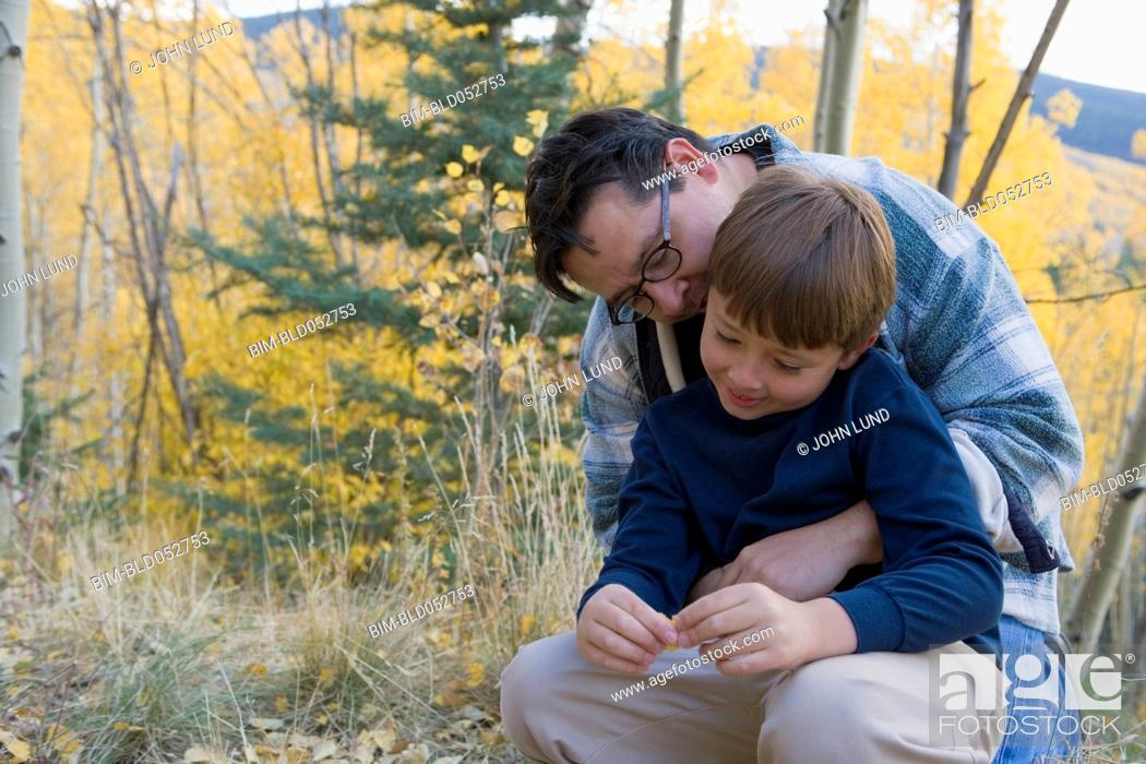 Stock Photo: Hispanic father hugging son in woods.