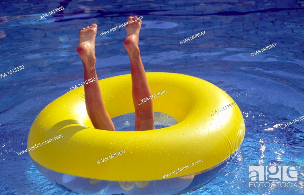 Stock Photo: Child's legs in the air playing in swimming pool in yellow ring.