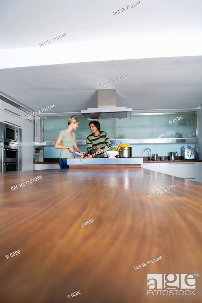 Stock Photo: Young couple in modern kitchen, cooking together, smiling.