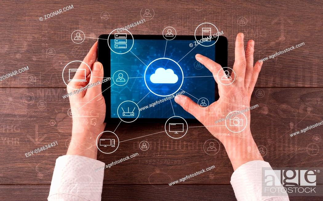 Imagen: Hand touching tablet with cloud computing and online storage concept.