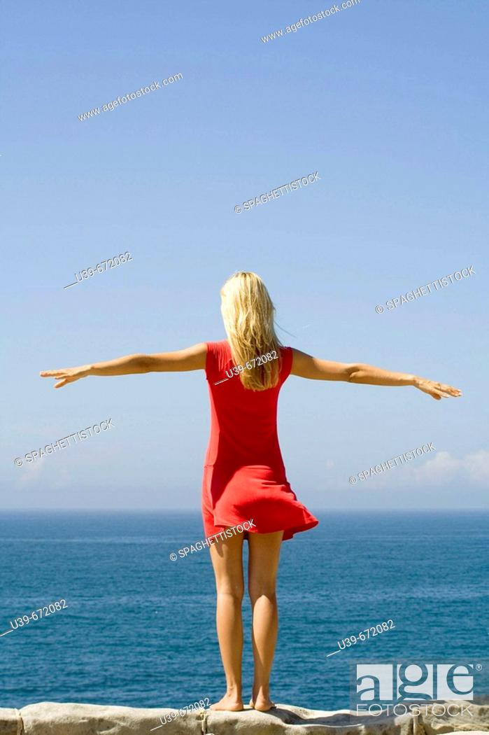 Stock Photo: Woman standing on a wall overlooking the sea. Shot from behind. Sydney, Australia.
