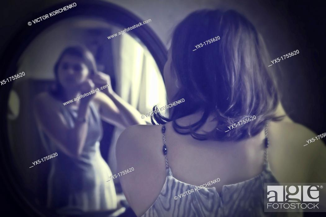 Stock Photo: Young woman in front of the mirror.