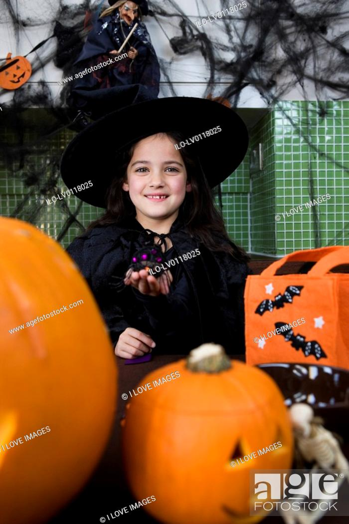 Stock Photo: Little girl in a witch's outfit at a Halloween party.