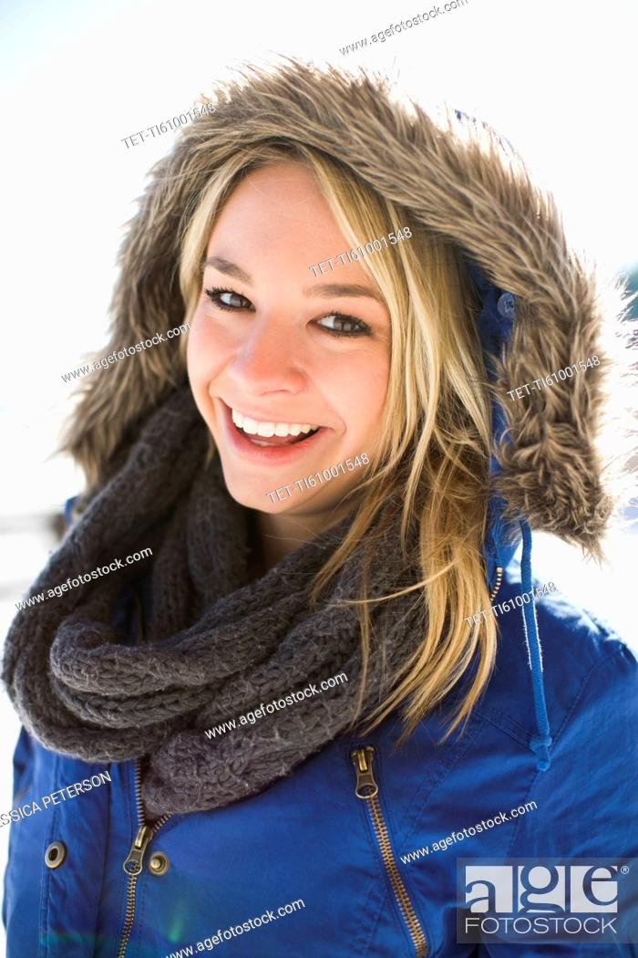 Stock Photo: Portrait of smiling young woman in winter coat hood.