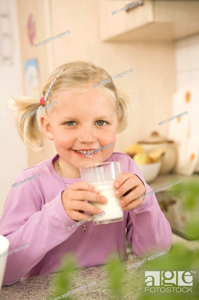 Stock Photo: Girl drinking glass of milk, smiling, portrait.