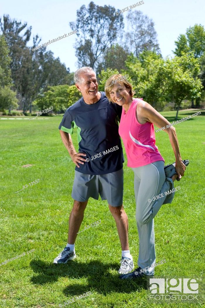 Stock Photo: Mature couple exercising in park, woman stretching, portrait.