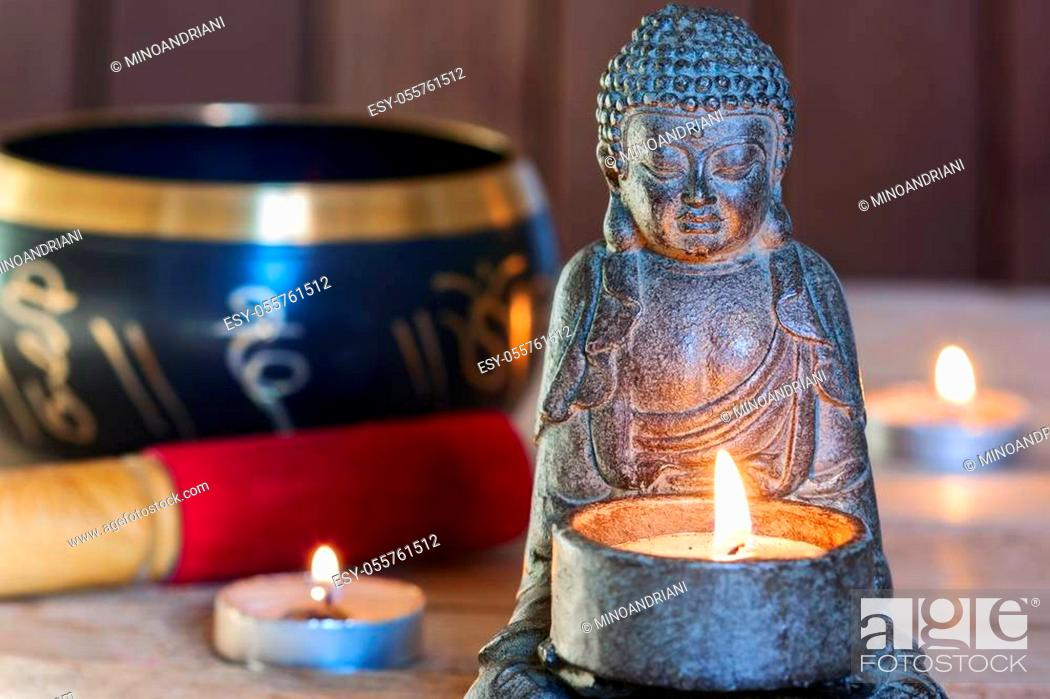 Stock Photo: stone sitting buddha, candles and Tibetan bowl. Around the candle, the atmosphere for meditation. Home comfort and relaxation.