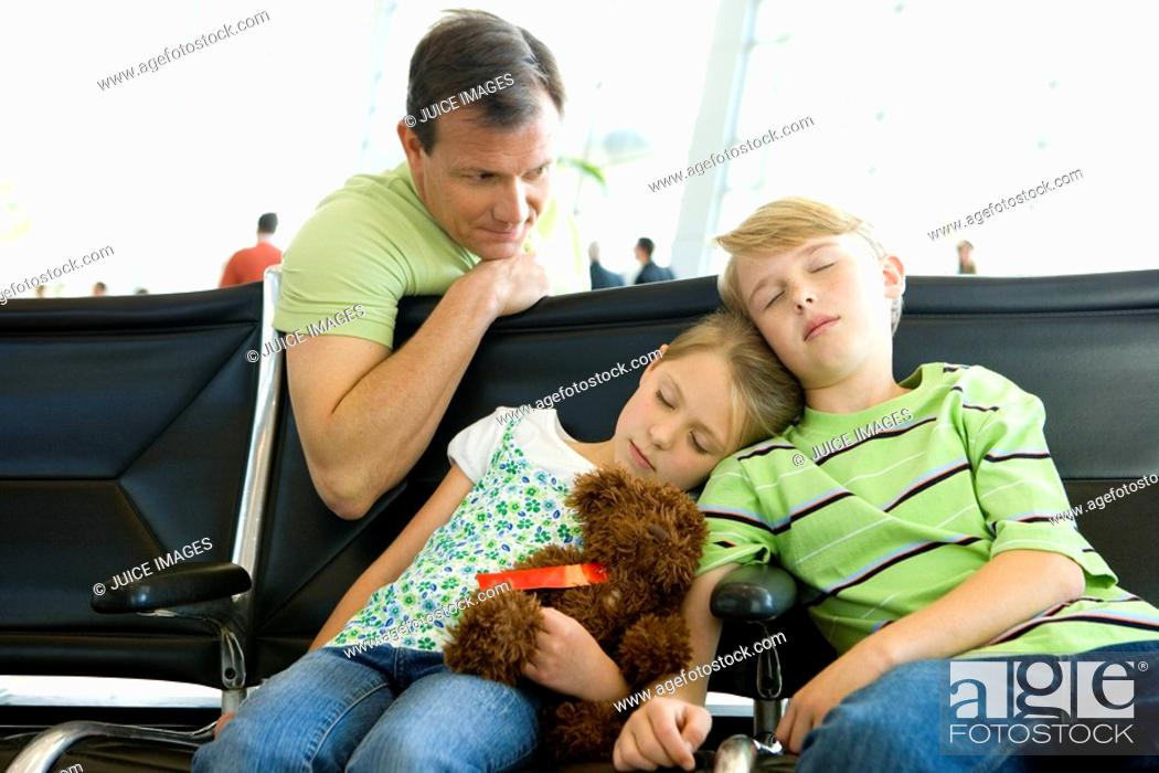 Stock Photo: Father looking at children sleeping on seats in airport departure lounge, girl 7-9 holding soft toy.