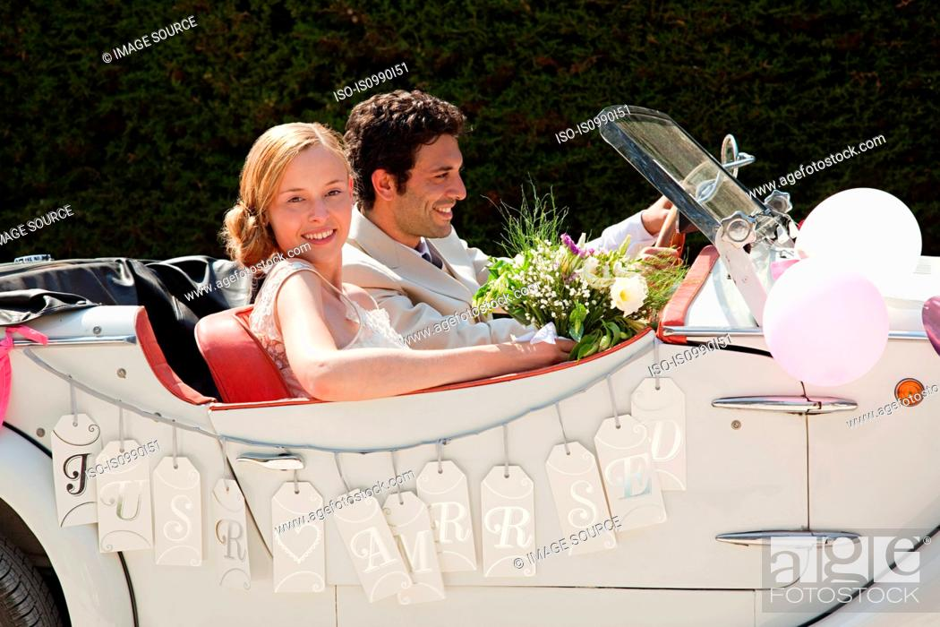 Stock Photo: Newlyweds leaving for honeymoon in vintage car.