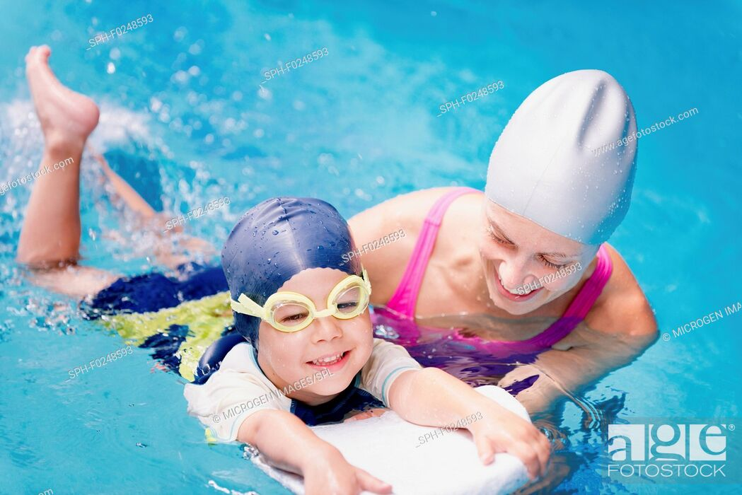 Stock Photo: Little boy learning to swim with swimming instructor.