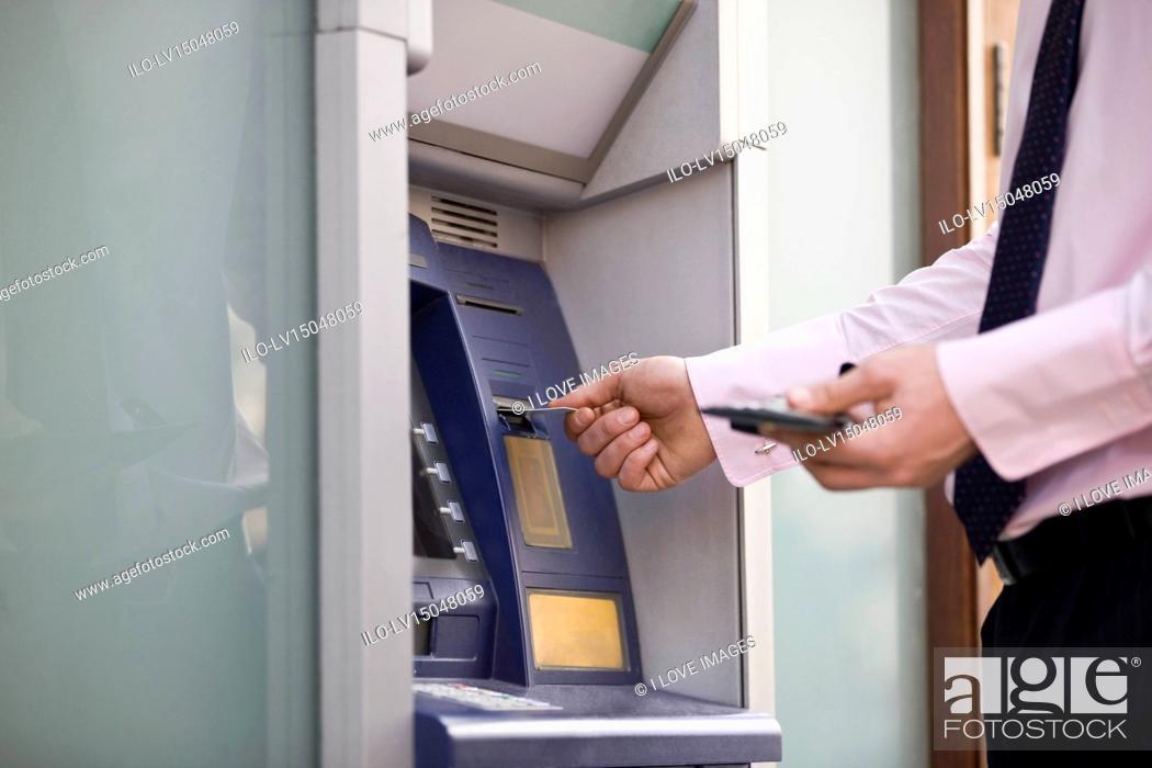 Stock Photo: A businessman using a cash machine.