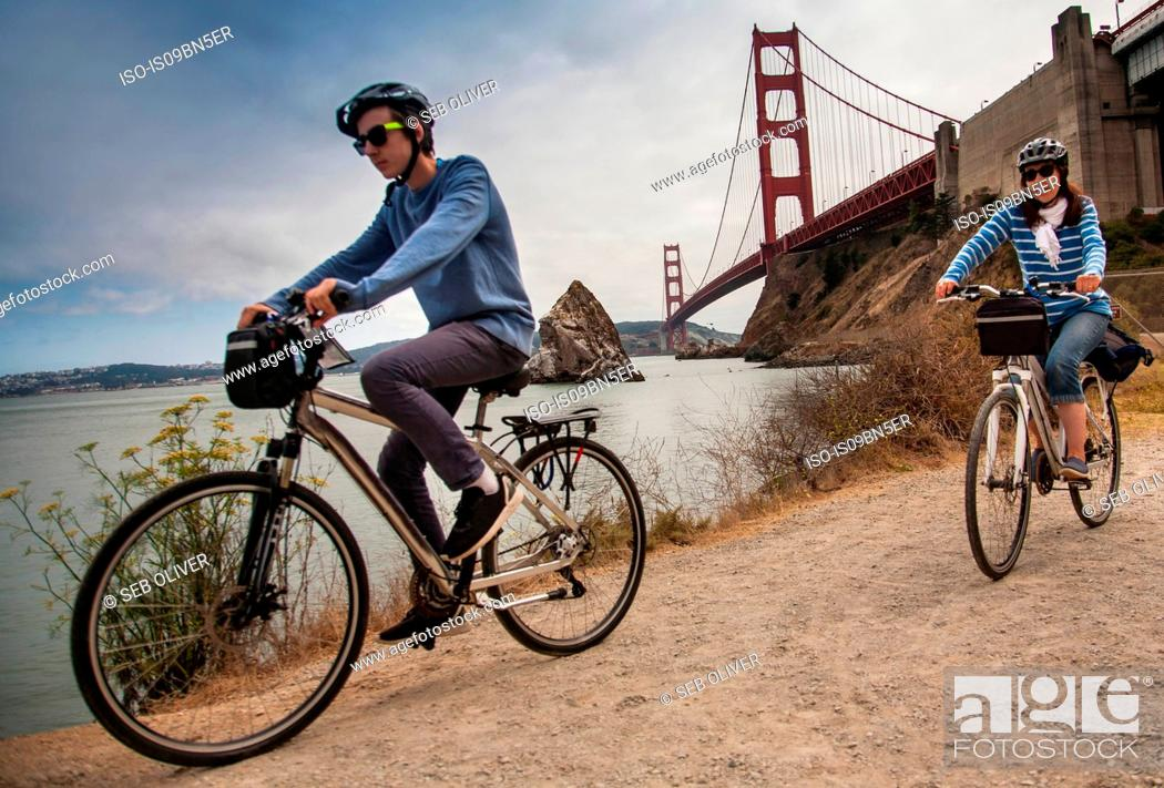 Stock Photo: Tourists cycling, Golden Gate Bridge in background, San Francisco, USA.
