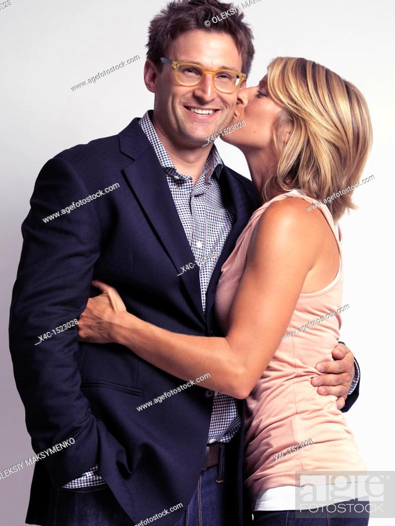 Stock Photo: Smiling casually but with style dressed young people  Woman kissing a man on the cheek  Isolated on gray background.