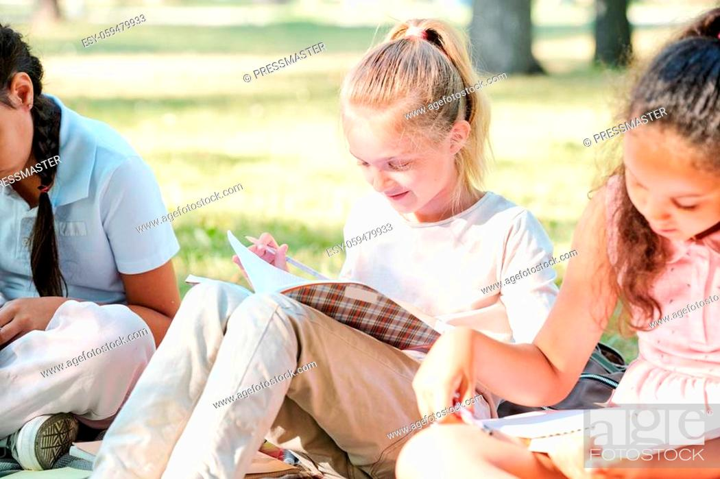 Stock Photo: Curious blond girl sitting among classmates and checking notes in workbook while doing task.