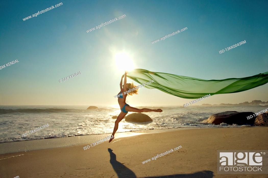 Photo de stock: Dancer leaping on a beach.