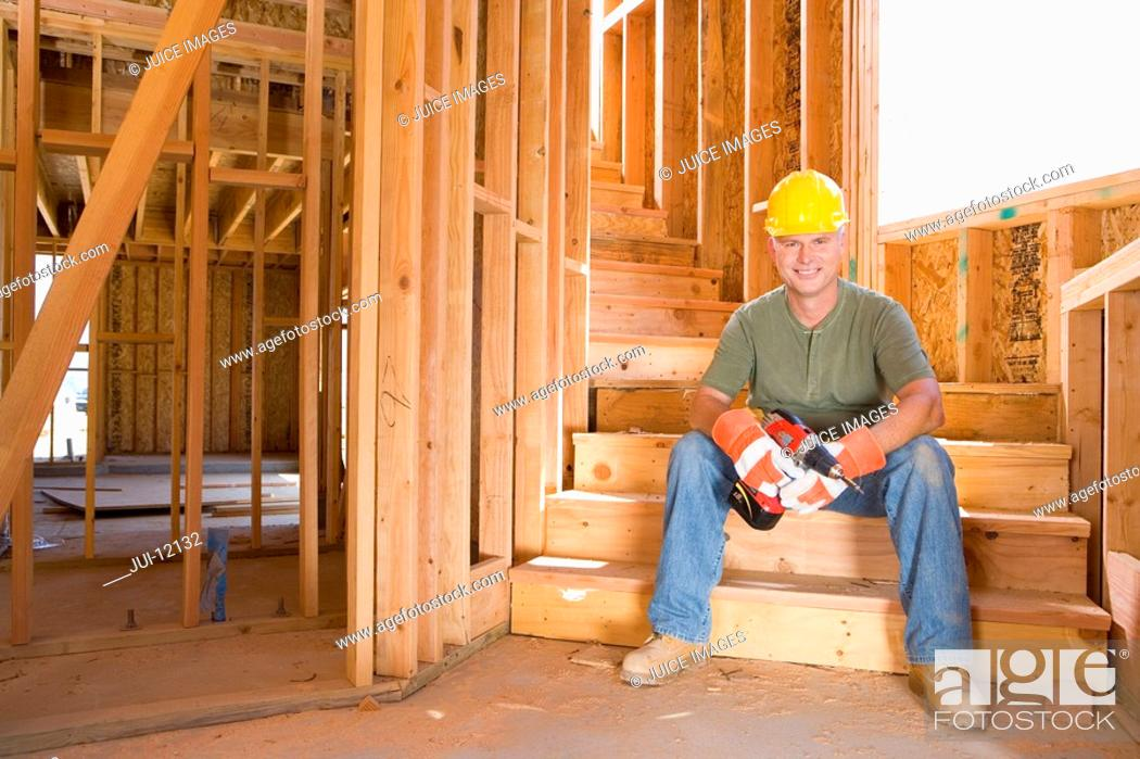 Stock Photo: Builder in hardhat on steps on site, smiling, portrait.