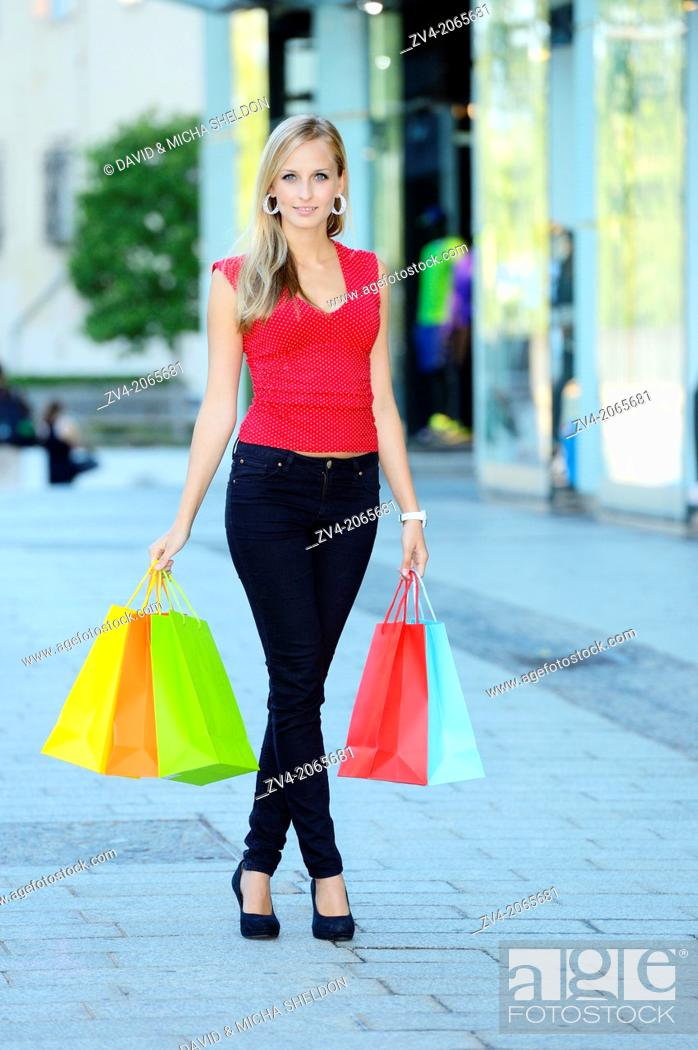 Stock Photo: Young woman shopping in a town outdoors.