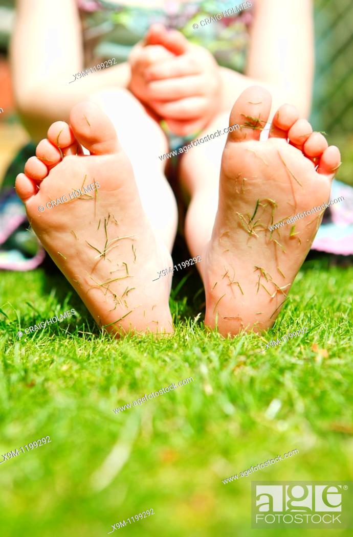 Stock Photo: Four year old girl in a garden with grass cuttings on the soles of her feet.