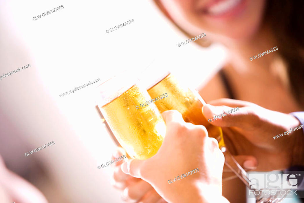 Stock Photo: Close-up of two men and a woman toasting champagne flutes.