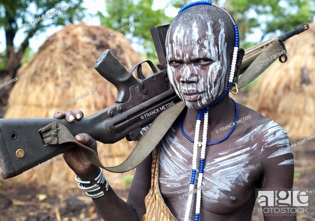 Stock Photo: Woman belonging to the Mursi tribe. Omo valley ( Ethiopia). She is holding a Kalashnikov.
