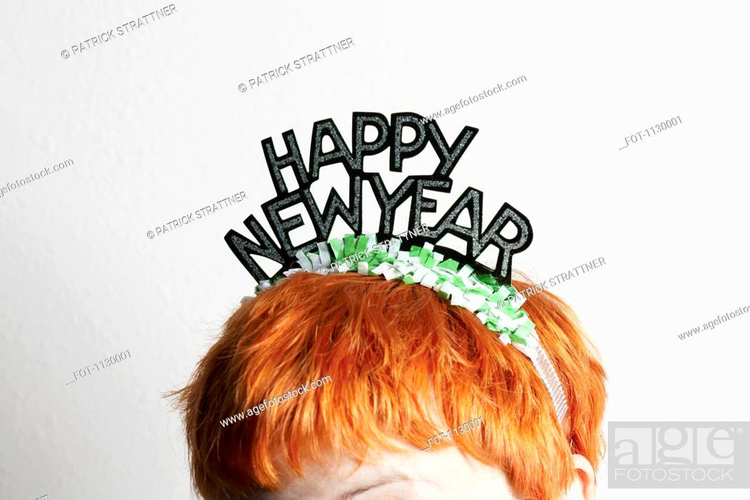 Stock Photo: A woman wearing a party tiara with Happy New Year on it, top of head.