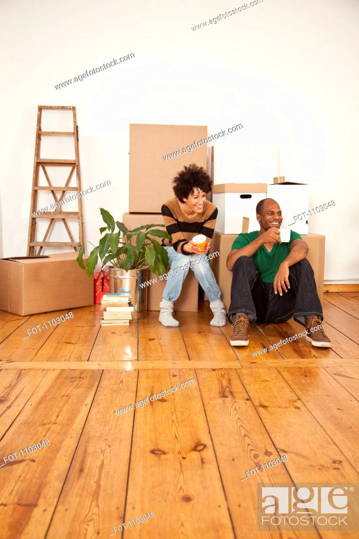 Stock Photo: A laughing couple taking a coffee break while moving house.