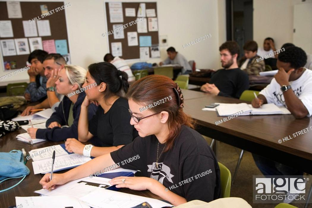 Stock Photo: College students sitting at tables in classroom.