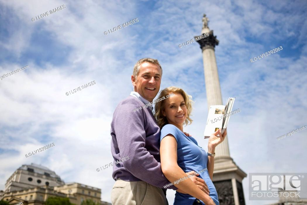 Stock Photo: A middle-aged couple in front of Nelson's column, holding a guidebook.