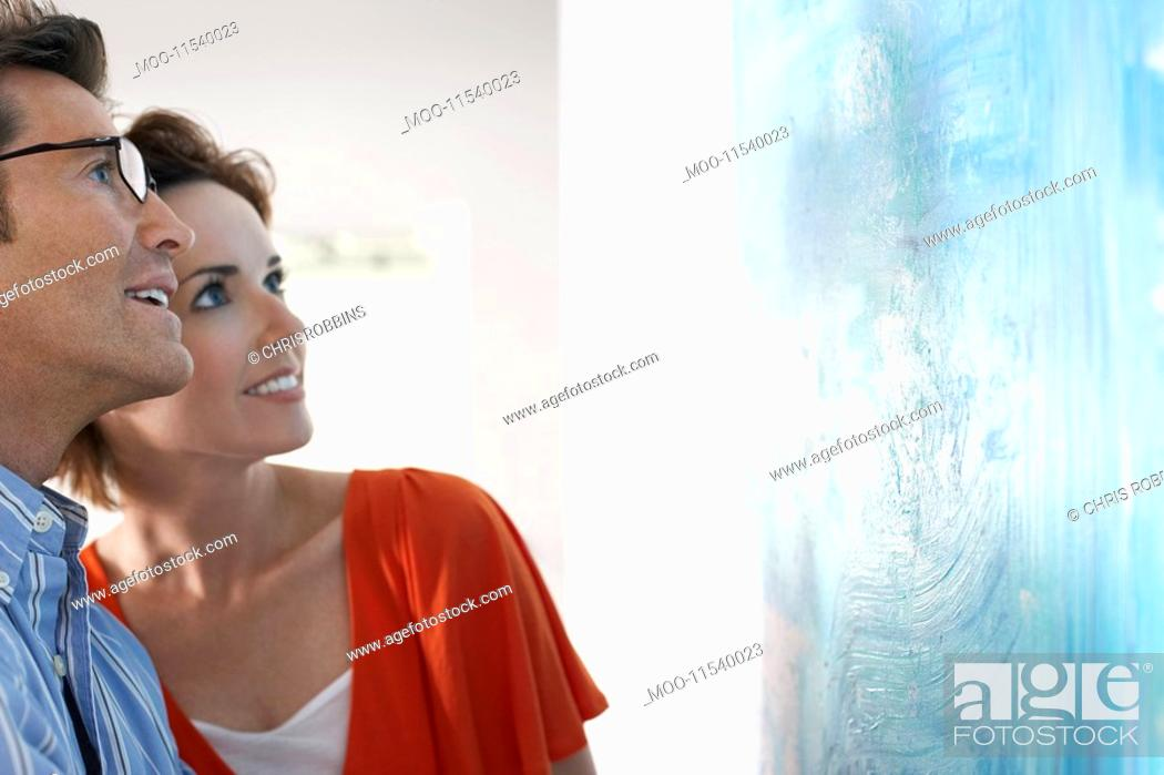 Stock Photo: Couple looking at modern art painting in gallery.