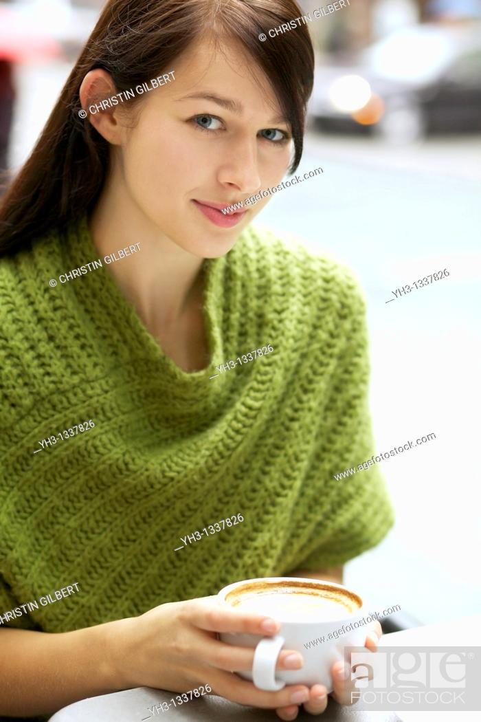 Stock Photo: Beautiful young woman relaxing with her cappuccino outdoor.