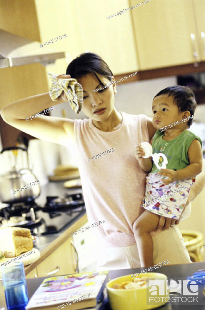 Stock Photo: Mother carrying her son in the kitchen.