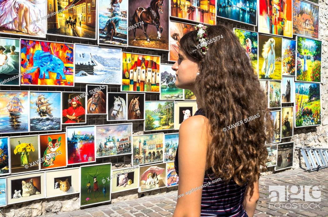 Imagen: Girl looking at the paintings exhibited in the Medieval Fortification, Krakow, Poland.