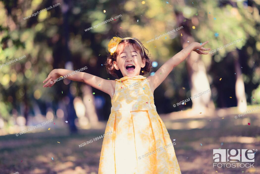 Stock Photo: Portrait of a little girl running and playing in the park wearing a beautiful dress.