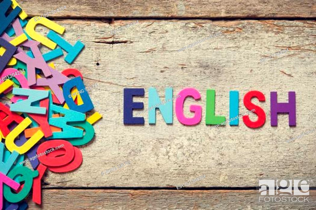 "Photo de stock: The colorful words ""ENGLISH"" made with wooden letters next to a pile of other letters over old wooden board."